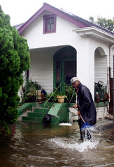 MAN CLEANS STROM DRAIN IN FLOODED NEW ORLEANS NEIGHBORHOOD IN WAKE OFTROPICAL STORM ISIDORE.