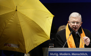 A bodyguard gets an umbrella to protect Hesse's state Prime Minister Roland Koch from tomatoes and eggs being thrown during an election campaign rally in Frankfurt