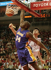 SHAQUILLE ONEAL DUNKS THE BALL OVER CHINESE CENTER YAO MING IN HOUSTON.