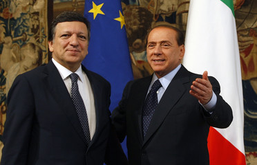 Italian Prime Minister Berlusconi waves next European Commission President Barroso during a meeting at Palazzo Chigi in Rome