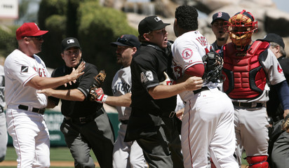 Home plate umpire Paul Schreiber holds back Los Angeles Angels of Anaheim's Bobby Abreu in Anaheim