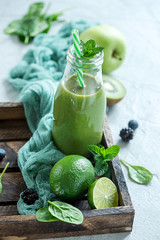 Green smoothie wtih spinach and lime, healthy detox vitamin diet or vegan food concept