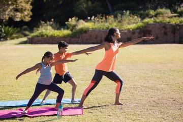 Female trainer with children practicing Virabhadrasana II pose