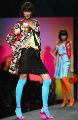 A MODEL WEARS AN EMBROIDERED JACKET WITH SKIRT AND TURQUOISESTOCKINGS AS PART OF MOSCHINO'S ...