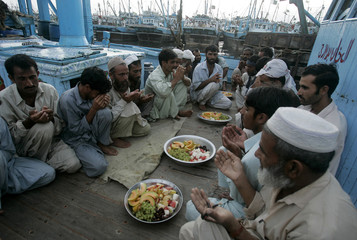 Fishermen offer prayers before breaking of fast on the first day of Ramadan in Karachi