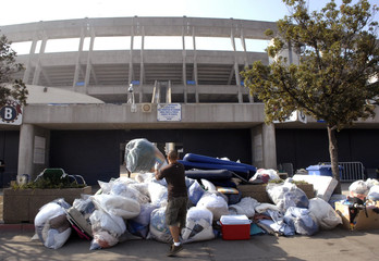 Volunteers help clean up donated items as evacuees displaced by wildfires leave Qualcomm Stadium for other facilities in San Diego
