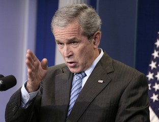 U.S. President Bush gestures during a news conference in the White House press room in Washington