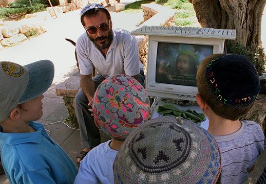 JEWISH SETTLERS WATCH PALESTINIAN PROPAGANDA ON COMPUTER SCREEN IN BEIT EL.