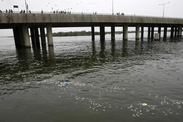 People look at dead fish surfacing on sea water at Keemari harbour in Karachi