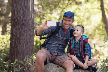 Happy father sitting with boy on rock taking selfie