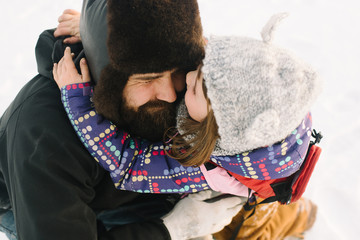 Girl hugging father in snow