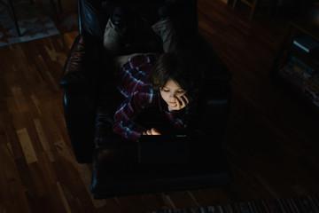 Boy reclining on armchair