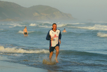ENGLAND'S FLINTOFF JOGS ALONG THE BEACH AT EAST LONDON BEFORE DEPARTINGFOR THE OPENING ...
