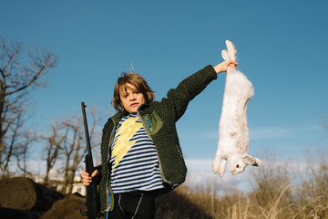 Boy holding up dead rabbit and holding a rifle