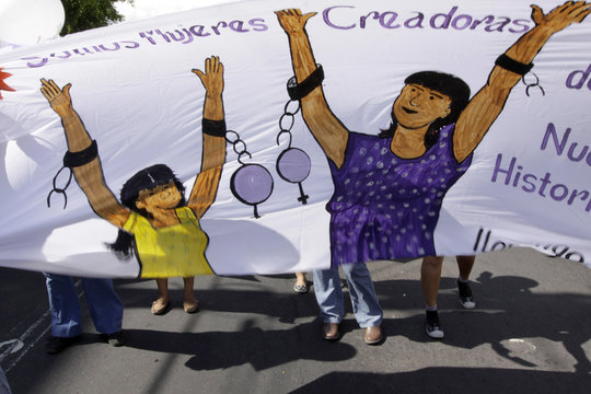 """An image on a banner reads, """"We Are Creative Women"""", as women take part in a march to celebrate the """"Day of No Violence Against Women"""" in San Salvador"""