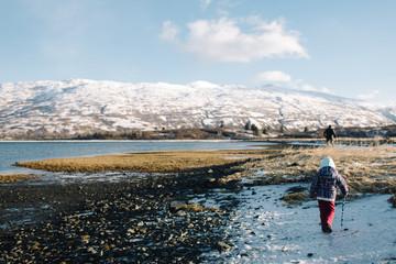 Girl walking in water near mountain landscape