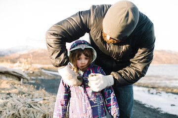 Father putting coat on little girl