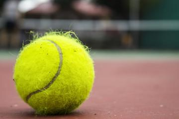 Yellow tennis ball on red court. Fluffy felt tennis ball closeup photo.