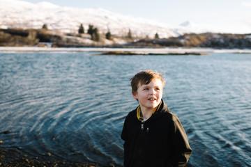 Boy standing near lake