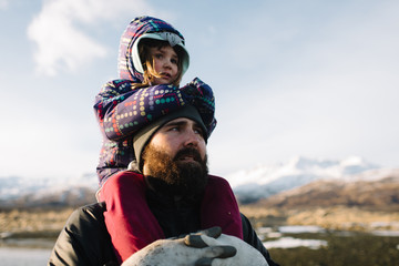 Girl sitting on her father's shoulders