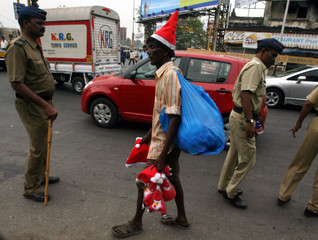 A street hawker selling Christmas hats and Santa Claus toys walks past Indian policemen standing guard during busy traffic in Mumbai