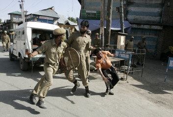 An Indian policeman holds onto a Kashmiri protester as another raises his baton during a protest in Shopian