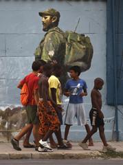 Boys walk by mural showing Cuba's former leader Fidel Castro in Havana