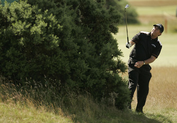 Mickelson of the U.S. plays from behind bushes on the 15th hole during a practice session at the 2007 British Open Golf Championship in Carnoustie