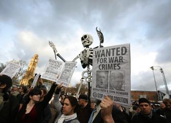 Demonstrators hold signs while protesting against U.S. President George W. Bush and Australian Prime Minister John Howard outside Sydney's Central Station