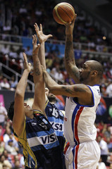 Peter John Ramos of Puerto Rico attempts to shoot over the Argentinan defense during second half of men's FIBA Americas Championship quarterfinals basketball game in San Juan