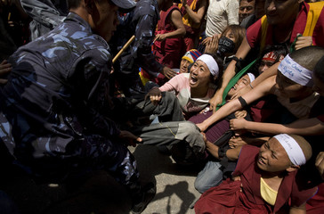 Riot police try to detain Tibetan activists protesting outside the visa section of the Chinese consulate in Kathmandu