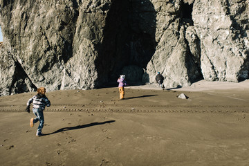 Children playing near cave on beach