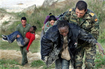 Spanish non-commissioned officer and soldiers help to carry several illegal immigrants who were foun..