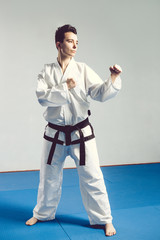 girl in karate suit kimono in studio at grey background. Female child shows judo or karate stans in white uniform with black belt. Individual martial art sport . body portrait
