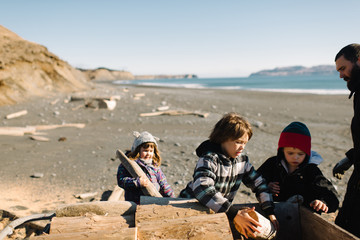 Children and father playing on beach
