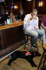 U.S. Army Specialist Keck drinks a beer at a bar with his new service dog Nolls at his feet after they graduated from the NEADS program in Boston