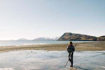 Boy walking with stick on beach