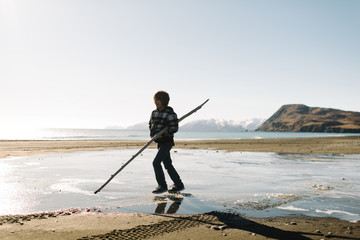 Boy playing with stick on beach