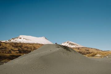 Boy sitting atop sand hill near mountains