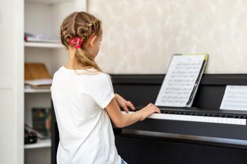 Girl at piano lesson at home