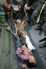 Indian army soldiers carry the injured in Badami Bagh Cantonment in Srinagar