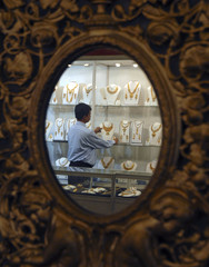A staff displays gold necklaces at the Zak Jewels India Exhibition 2009 in the southern Indian city of Chennai