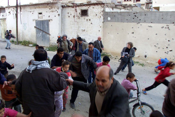 Palestinian escape after Israeli troops opened fire at them during the visit of Pierre Sane, Secreta..