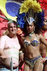 A WOMAN DRESSED IN CARNIVAL COSTUME STANDS WITH A SLOVENIAN SUPPORTER.