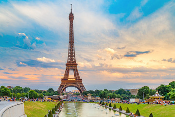 Eiffel tower, view from Trocadero park over fountain. People making their evening promenade around fountain. Eiffel tower is famous symbol of Paris city and France. Sunset scenery, epic dramatic sky.