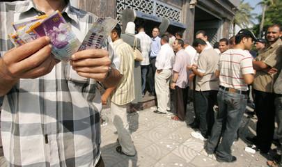 Palestinians wait in line at a cash machine in Gaza