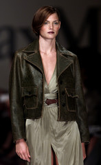 A model wears a brown leather jacket over a green dress as part of the Max Mara Spring/Summer ready-..