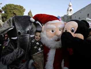A Palestinian boy poses for a picture with people wearing costumes during a Christmas parade in Bethlehem