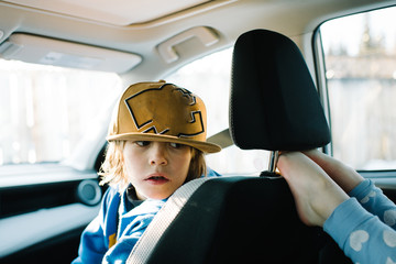 Boy in car looking at barefoot child in backseat