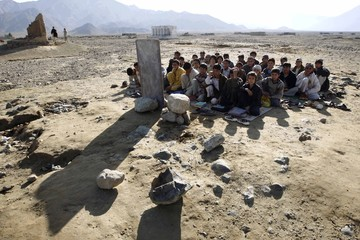 Afghan boys sit on the ground outdoors for their lesson near Khas Kunar refugee camp
